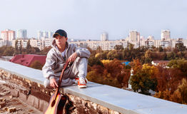 Hombre joven en el tejado con una guitarra Imagen de archivo libre de regalías