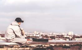 Hombre joven en el tejado con una guitarra Fotos de archivo