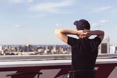 Hombre joven en el tejado de un edificio alto Fotografía de archivo