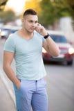 Hombre joven en el teléfono celular en la calle de la ciudad Fotos de archivo libres de regalías