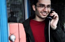Hombre joven en el teléfono público imagenes de archivo