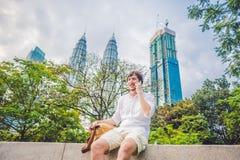 Hombre joven en el teléfono Vistiéndose en una camisa blanca, pantalones cortos beige El hombre de negocios hermoso joven en ropa Fotos de archivo