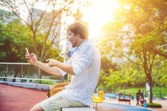 Hombre joven en el teléfono Vistiéndose en una camisa blanca, pantalones cortos beige El hombre de negocios hermoso joven en ropa Fotografía de archivo