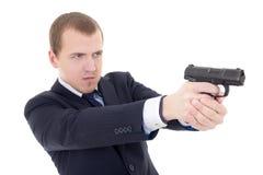 Hombre joven en el tiroteo del traje de negocios con el arma aislado en blanco Foto de archivo libre de regalías