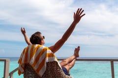 Hombre joven en el traje de ba?o que se relaja en una terraza y que disfruta de la libertad en un destino tropical Brazos levanta foto de archivo
