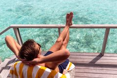 Hombre joven en el traje de ba?o que se relaja en una terraza y que disfruta de la libertad en un destino tropical imagenes de archivo