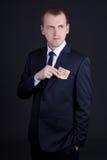 Hombre joven en el traje de negocios que pone el billete de banco euro en el bolsillo Imagen de archivo libre de regalías