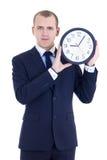 Hombre joven en el traje de negocios que sostiene el reloj de la oficina aislado en pizca Fotografía de archivo libre de regalías