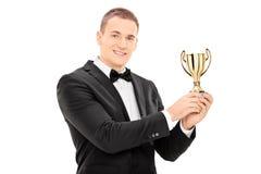 Hombre joven en el traje que sostiene un trofeo foto de archivo