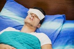 Hombre joven en fiebre de medición de la cama con el termómetro Foto de archivo libre de regalías