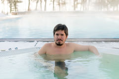 Hombre joven en Jacuzzi de la bañera al aire libre en el invierno Imagen de archivo