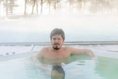 Hombre joven en Jacuzzi de la bañera al aire libre en el invierno Imagen de archivo libre de regalías