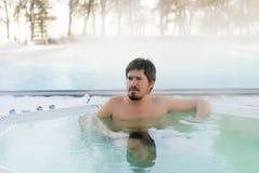 Hombre joven en Jacuzzi de la bañera al aire libre en el invierno Foto de archivo
