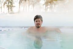 Hombre joven en Jacuzzi de la bañera al aire libre en el invierno Fotos de archivo