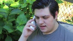 Hombre joven en jardín en el teléfono almacen de metraje de vídeo