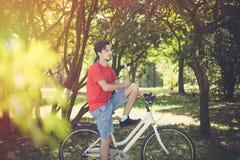Hombre joven en la bici en madera con la botella de reclinación del agua foto de archivo libre de regalías