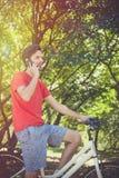 Hombre joven en la bici en madera con smartphone fotografía de archivo
