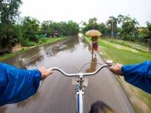 Hombre joven en la bicicleta debajo de la lluvia Imagenes de archivo