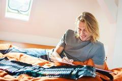 Hombre joven en la cama, dibujando en libro de colorear Imágenes de archivo libres de regalías
