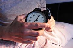Hombre joven en la cama que fija el despertador Fotografía de archivo libre de regalías