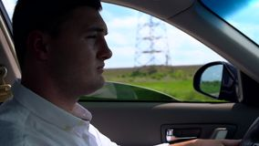 Hombre joven en la camisa blanca que conduce un vehículo metrajes