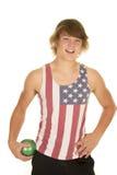 Hombre joven en la camisa de la bandera que sostiene la bola verde Imágenes de archivo libres de regalías