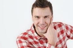 Hombre joven en la camisa del inconformista que lleva a cabo la mano en la barbilla y la situación contra el fondo blanco foto de archivo