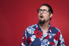 Hombre joven en la camisa hawaiana que mira hacia arriba con la boca abierta Imágenes de archivo libres de regalías