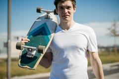 Hombre joven en la camiseta blanca que sostiene longboard o el monopatín en el skatepark fotos de archivo libres de regalías