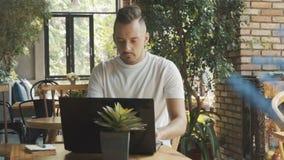 Hombre joven en la camiseta blanca que trabaja en el ordenador portátil moderno en café Trabajo del hombre de negocios sobre el o almacen de video