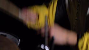 Hombre joven en la chaqueta amarilla que juega los tambores en la oscuridad 4K almacen de video