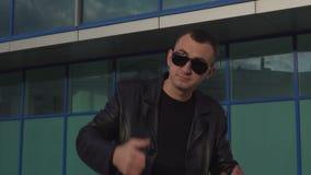 Hombre joven en la chaqueta de cuero y gafas de sol que se colocan al aire libre y hombre que invita alguien almacen de metraje de vídeo