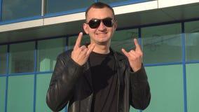 Hombre joven en la chaqueta de cuero y las gafas de sol que se colocan muestra al aire libre y de las demostraciones de los cuern metrajes