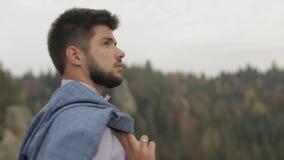 Hombre joven en la colina de una montaña con la chaqueta Hombre de negocios Novio prepare almacen de metraje de vídeo