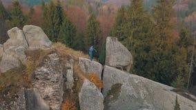 Hombre joven en la colina de una montaña Hombre de negocios Novio prepare aéreo metrajes