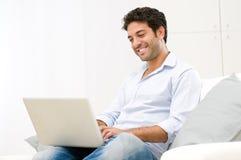 Hombre joven en la computadora portátil Fotografía de archivo