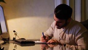 Hombre joven en la escritura del ordenador en la hoja de papel almacen de metraje de vídeo