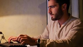 Hombre joven en la escritura del ordenador en la hoja de papel almacen de video