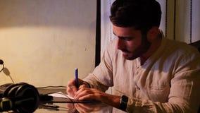 Hombre joven en la escritura del ordenador en la hoja de papel metrajes