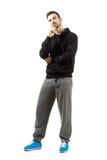 Hombre joven en la mirada de pensamiento de la sudadera con capucha y de la ropa de deportes para arriba Imagen de archivo