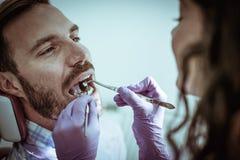 Hombre joven en la oficina femenina del dentista Imagen de archivo libre de regalías