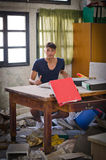 Hombre joven en la oficina muy sucia que parece desconcertada Foto de archivo libre de regalías