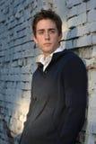 Hombre joven en la pared de ladrillo blanca Fotografía de archivo libre de regalías