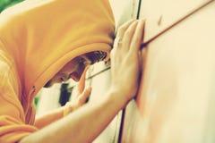 Hombre joven en la pared del grunge de la pintada Imagenes de archivo