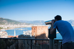 Hombre joven en la plataforma de observación que mira la visión panorámica con los prismáticos Imagenes de archivo