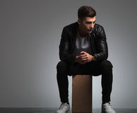 Hombre joven en la presentación negra de la chaqueta de cuero asentado en estudio Imagenes de archivo