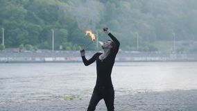 Hombre joven en la ropa negra que realiza una demostración con la situación de la llama en riverbank Exhalación experta del artis metrajes