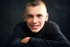 Hombre joven en la ropa negra, sonriendo imagen de archivo