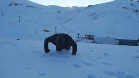 Hombre joven en la ropa oscura que cae abajo agotado en una montaña nevosa metrajes