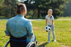 Hombre joven en la silla de ruedas que juega la bola con la hija foto de archivo libre de regalías